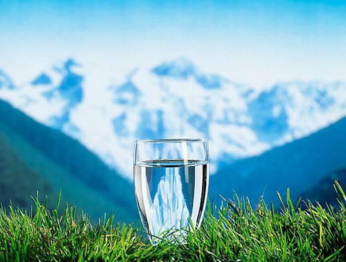 Важно пить воду: стакан чистой воды в горах на траве.
