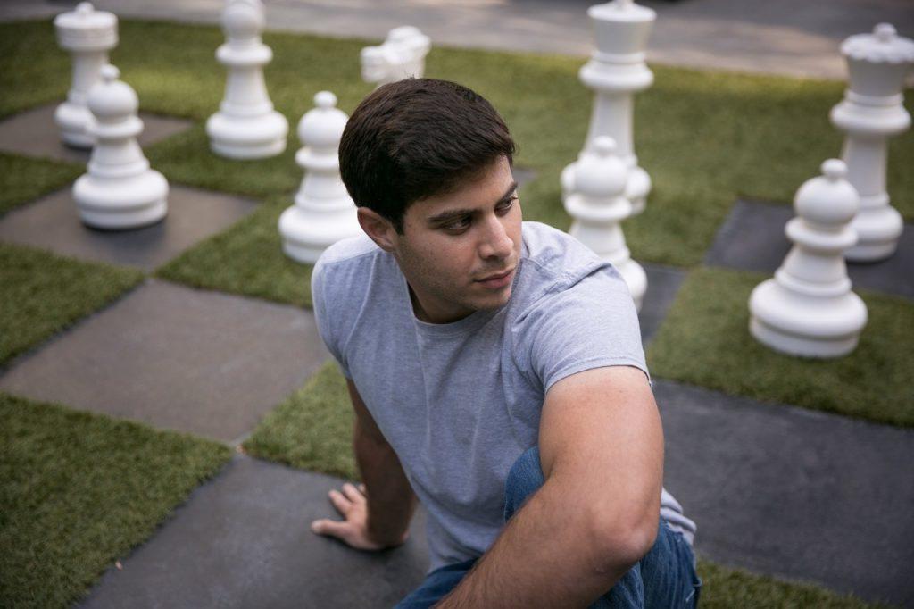 Макс Дойч сидит на большом шахматном поле