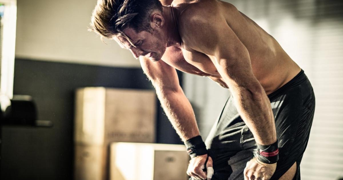 Уставший спортсмен стоит в азе и пытается отдышаться