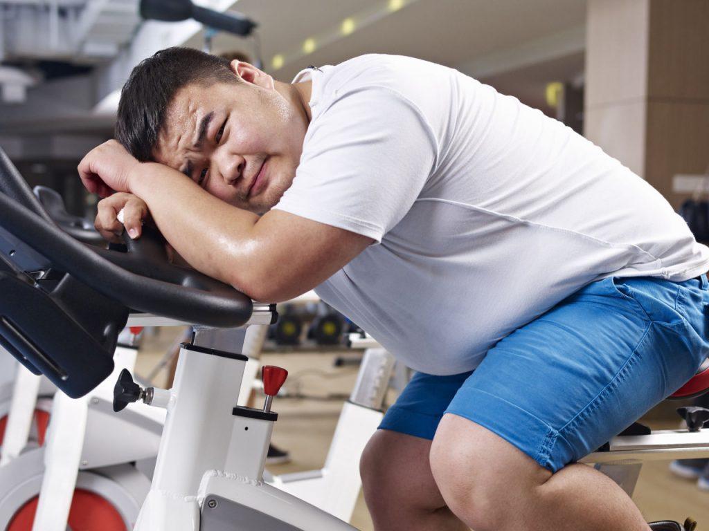 пухлый мужчина устал и лег на велотренажер
