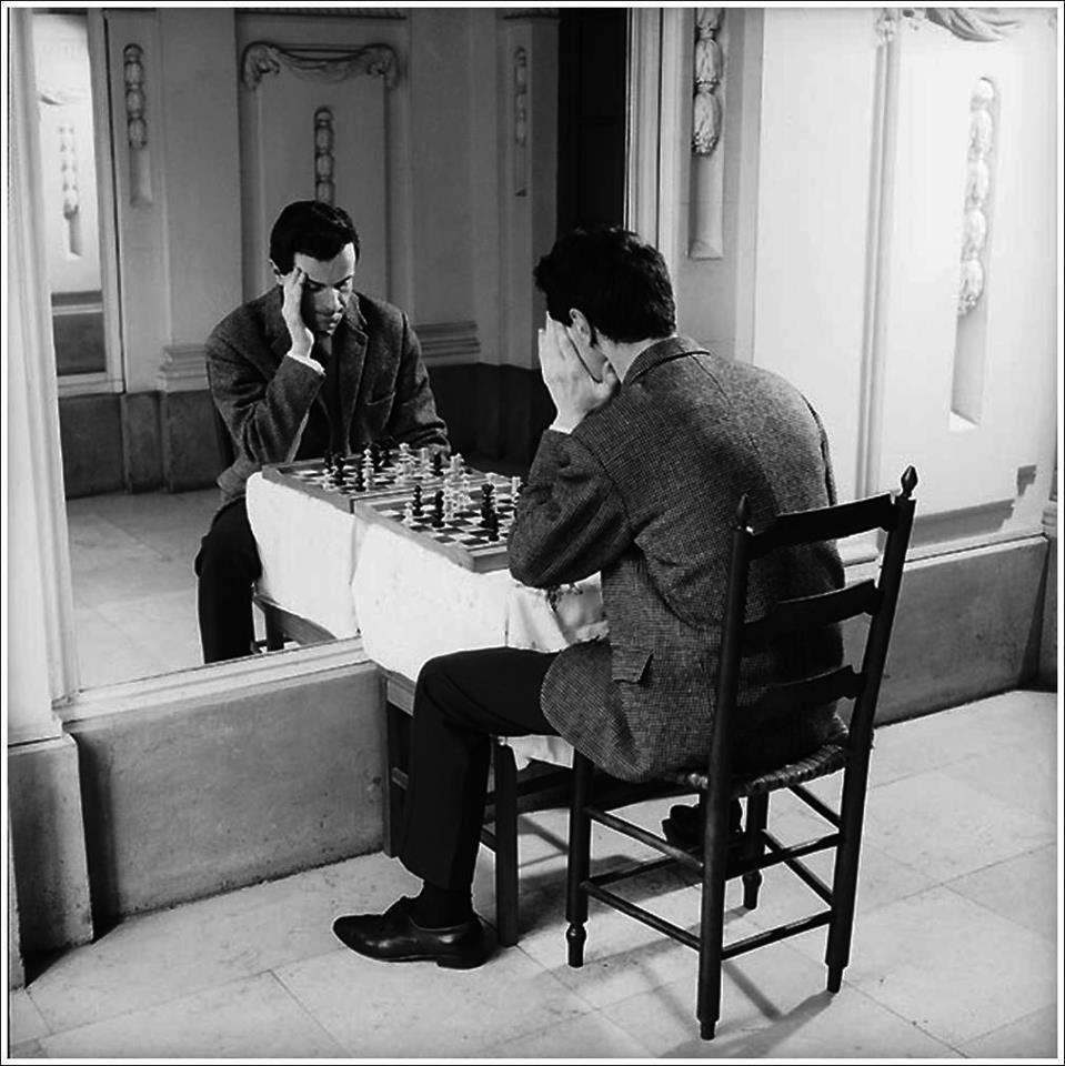 Человек играет в шахматы со своим отражением, он ведет преднамеренную практику