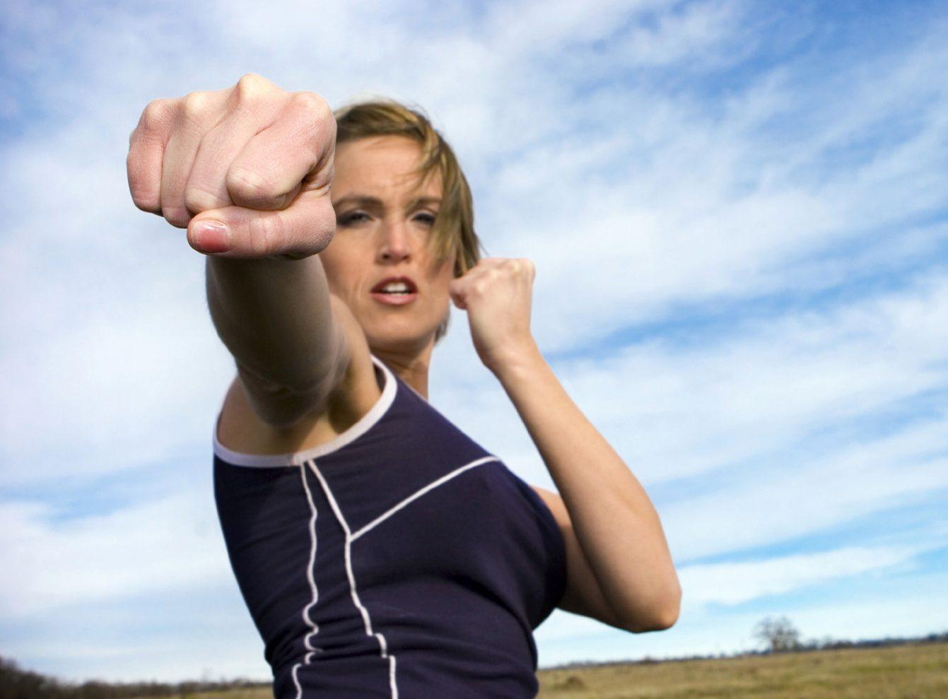 Женщина стоит в боевой стойке