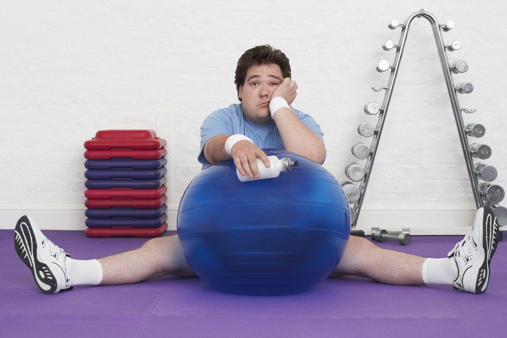спортсмен сидит в тренажерном зале и думает о своей подготовке