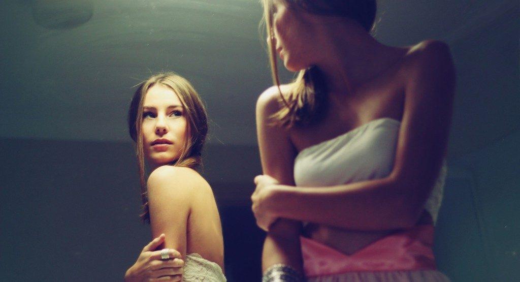девушка стоит перед зеркалом и пытается понять саму себя