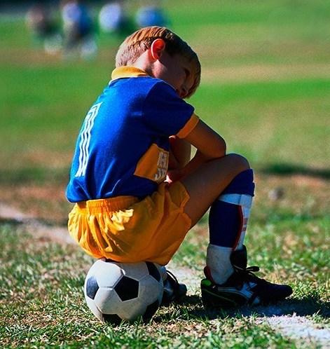 мальчик расстроен из-за своих неудач в футболе