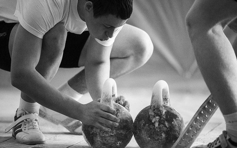 спортсмен старается подготовиться к соревнованиям и натирает гири тальком
