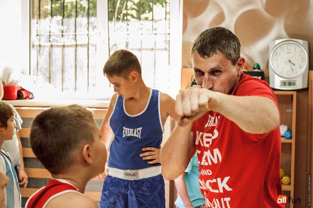Тренер следит за детьми в боксе